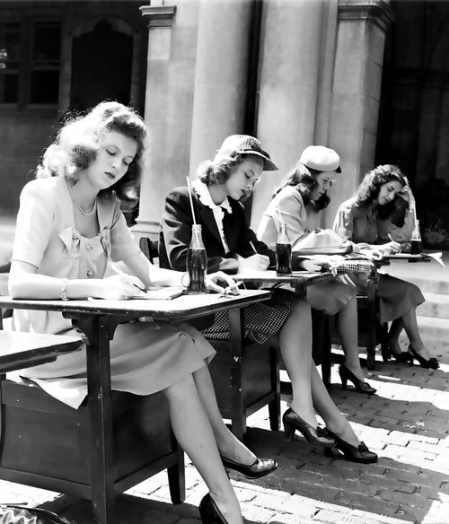 A group of 1940s female students doing their schoolwork outdoors.: