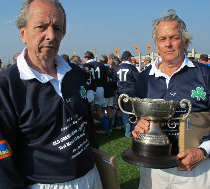 Survivors of the Andes plane crash Daniel Fernandez and Eduardo Strauch hold a commemorative trophy during a rugby game to mark the 40th anniversary of the incident, Santiago, Chile, October 13, 2012