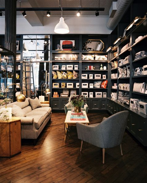 Dwell Studio NYC store - dark gray built-in shelving surrounds a seating area