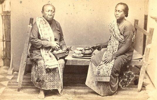 Dua wanita sedang minum teh di Soerabaia 1865-1880.