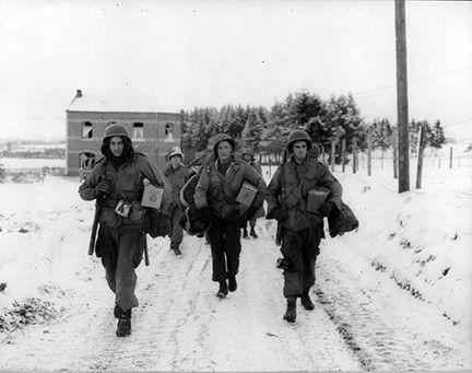 66-699 Pfc ML Dickens, East Omaha, Nebraska, Pvt Sunny Sundquist, Bremerton, Washington, Sgt Francis H. McCann, Middleton, Connecticut, de la 101e Division aéroportée près de Bastogne, en Belgique, se sont mis à rejoindre leur unité.  Janaury 11, 1945