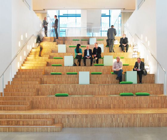 Vattenfall Arenastaden interior by Tengbom. On the ground floor of the building's atrium there is a common cafe and 'living rooms' on either side of the stairs, designed as bleachers with cushions and tables.