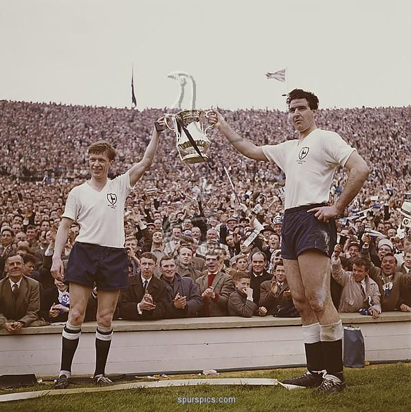 British professional footballers, John White (1937-1964) and Maurice Norman (right) hold the Football Association Challenge Cup (FA cup) trophy aloft in front of crowds after their team, Tottenham Hotspur beat Burnley FC at the FA cup final