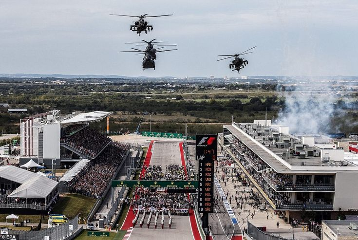 Military helicopters fly over during the national anthem before the start of the United States Formula One Grand Prix