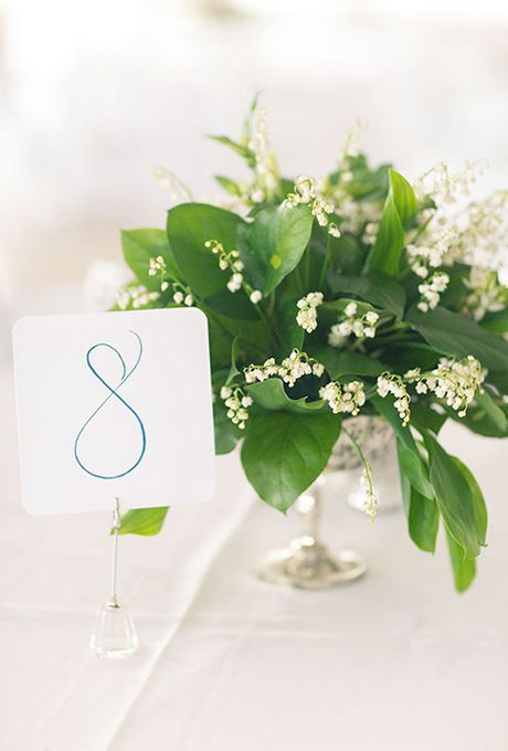 Simple Centerpieces with Lily of the Valley Flowers and Greenery. Lily of the ValleyJust one look at the tiny petals of this dainty bloom and its symbolism makes perfect sense: sweetness and purity of heart. It's also thought to represent a return to happiness.Featured In: Simple Centerpieces with Lily of the Valley Flowers and GreeneryPhoto:  Beach Productions