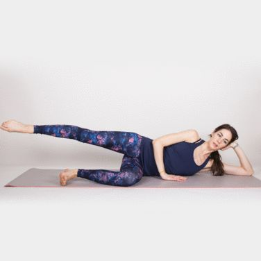 Pilates #workout #fitness | Lying on your left side, bring legs slightly in front of your hips to create a kickstand. Lift right leg to hip height and kick forward and back, maintaining upper body stability and pointing toes. Repeat for 10 reps. Then pause at hip height, point foot, and rotate in small circles (about the size of a tennis ball), circling 15 to 20 times in each direction.