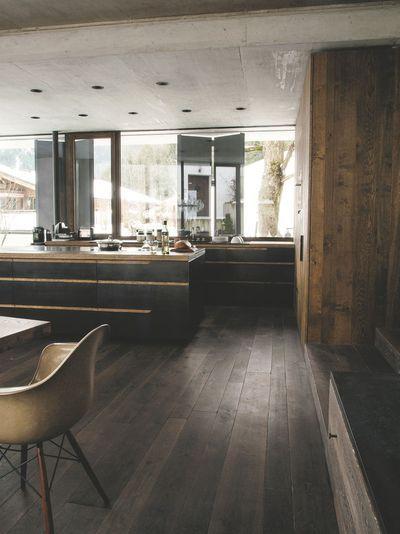La grande baie vitrée de cette cuisine en bois laisse entrer la lumière naturelle. Plus de photos sur Côté Maison http://petitlien.fr/7smq