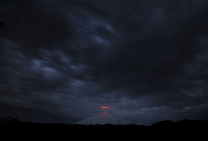 Вид на вулкан Вилльярика из города Пукон, Чили. Извергающийся с марта 2015-го вулкан Вилльярика расположен в Патагонских Андах и известен озером лавы, образовавшимся в его кратере после извержения 1985 года.