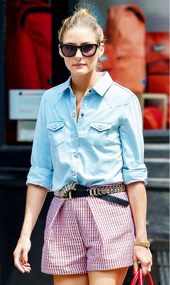Olivia Palermo wears a denim button-down, plaid shorts, and a leather and metal belt