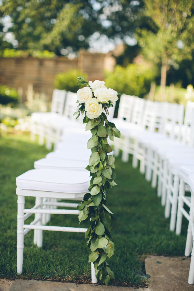 White ceremony chairs along the aisle were adorned with garlands of greenery embellished with soft, ivory roses. #weddingceremony #decor Photography: David & Tammy Molnar. Read More: https://www.insideweddings.com/weddings/an-exquisite-backyard-wedding-in-tennessee/532/