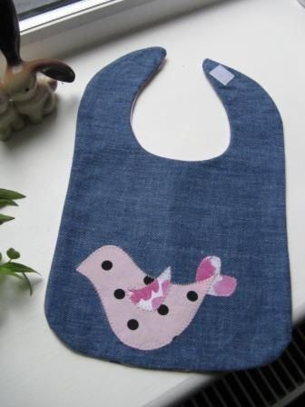 Applique denim bib backed with pink polka dot fabric.