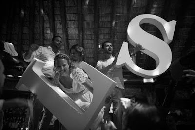 Bride & Groom dancing with the wedding decoration,the first letters of their names. A la carte Santorini weddings: Sabine & Luka - Their 4 days wedding in Santorini - Part III