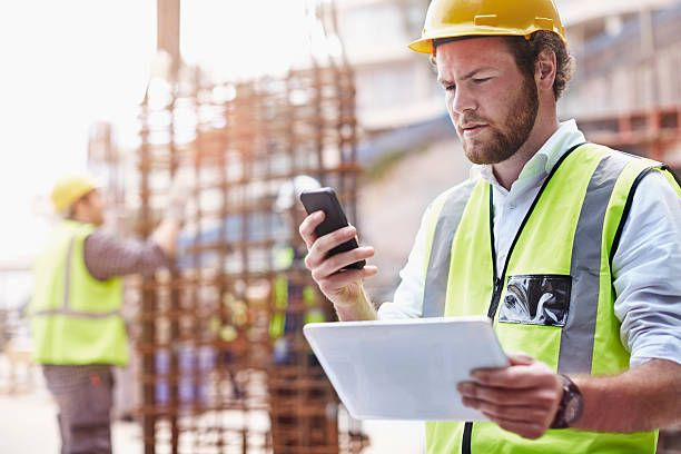 Construction Worker With Digital Tablet Texting With Cell Phone At Construction Site Cost Plus Contract Construction Images Construction Jobs