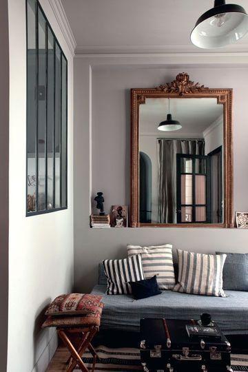 le coin salon avec dans la niche, un miroir de famille, une banquette-lit recouverte de tissu tissé main, Tensira chez Home Autour du monde, coussin noir, Caravane