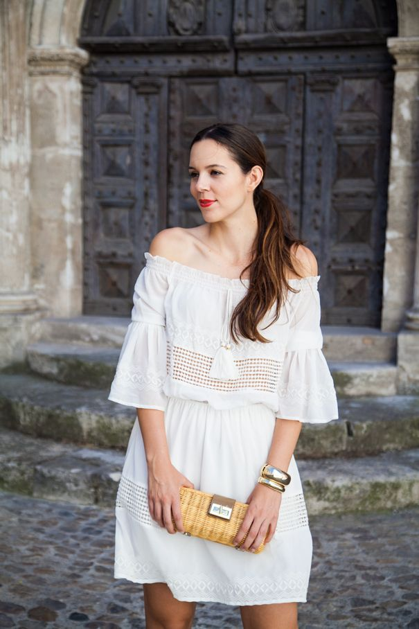 An off-the-shoulder white mini dress with straw accessories for a great casual summer look