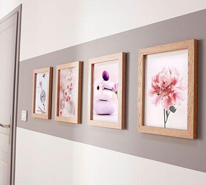 Peinte dans le prolongement de la porte et dans la même couleur subtile : une large bande met en valeur un alignement parfait de cadres en bois … Une idée déco à suivre pour habiller le mur d'un couloir par exemple.