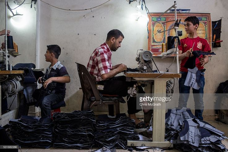 Syrian refugees work in a Syrian owned clothing factory on May 17, 2016 in Gaziantep, Turkey. Since fleeing the war and after the new E.U - Turkey deal effectively shutting down routes to Europe for many Syrian refugees, living in Turkey has become their only option, however there is very little stable work and little hope of building a future. Turkey's massive and largely unregulated garment industry is an attractive option for Syrians to work both legally and illegally despite low wages…