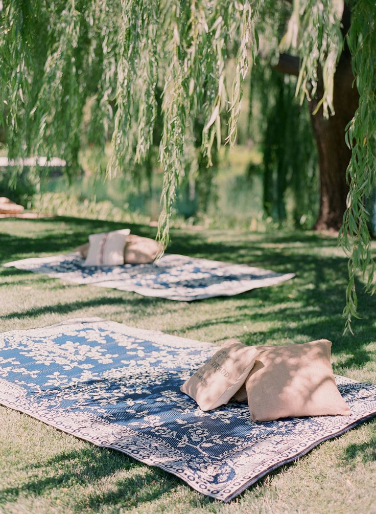 different way of outside living peaceful picnic blanket and pillows under a beautiful tree