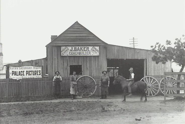 Outside blacksmith's shop - . Coach builder, horse shoer and general smith. Ernest John Baker third from left. Also an advertisement 'Every Saturday night Palace Pictures. Electric Biography Coy.' Camden, NSW 1910