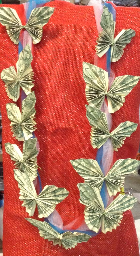 """A money lei made out of folded dollar bills. Each """"butterfly has (2) bills. Perfect for graduation!!!"""