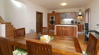 Kuchyňská linka příjemně zapadá do barevného přírodního stylu centrálního prostoru. Mezi ostrůvkem a linkou jsou francouzské dveře, vedoucí na terasu.