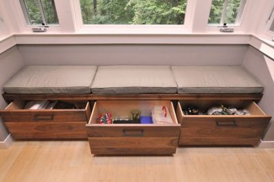 Custom built-in bench seating area with pull-out drawers under window in family room