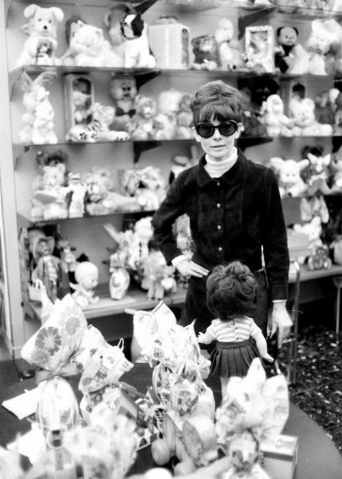 Audrey Hepburn photographed by Elio Sorci at a toy store in Rome (Italy), in March 1968. Audrey was wearing: • Ensemble: Yves Saint Laurent (of brown suede, jacket with buttons of metal and skirt, of his collection for the Autumn/Winter 1966/67). •...