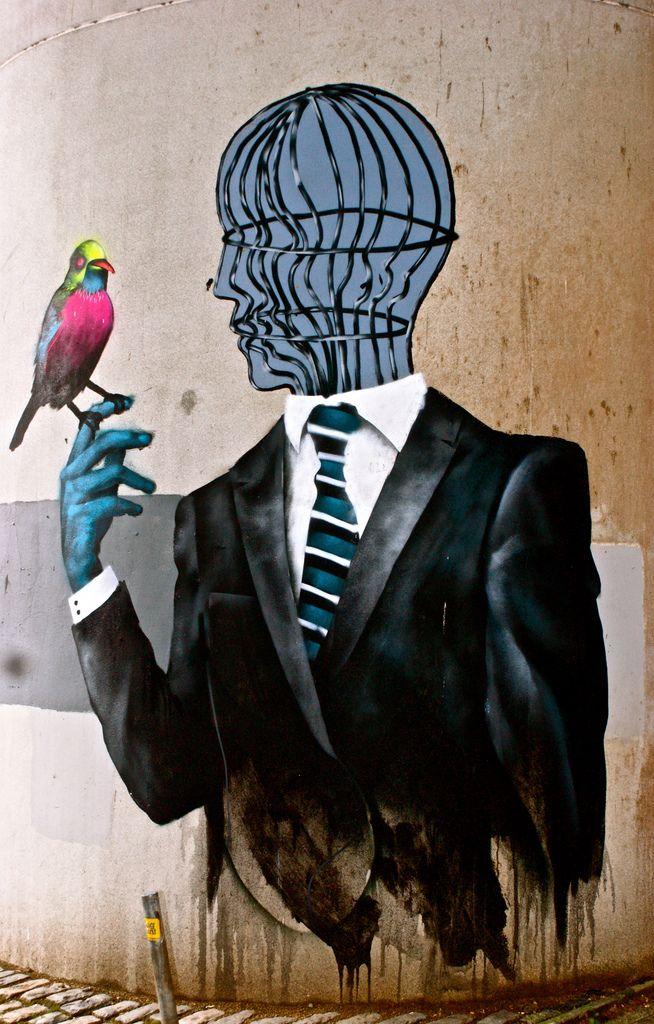 Bird on hand, cage in head - street art, bristol.