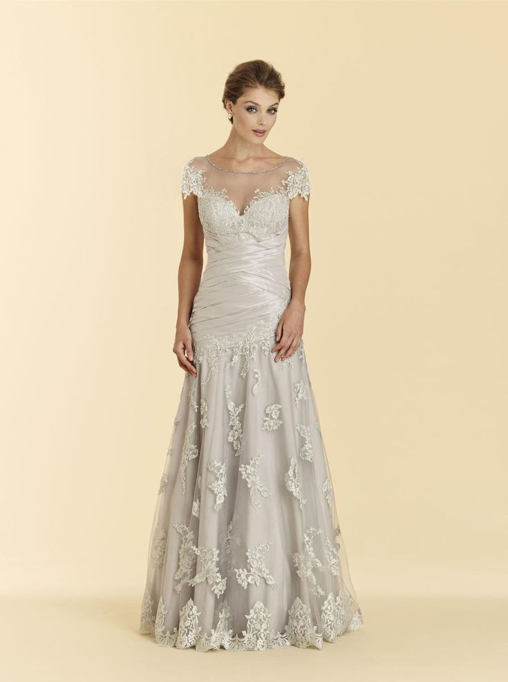 Rina Di Montella 2009 Cap sleeve soft taffeta and lace floor length mother of the bride dress features a sheer top with lace designs. Matching shawl is included.