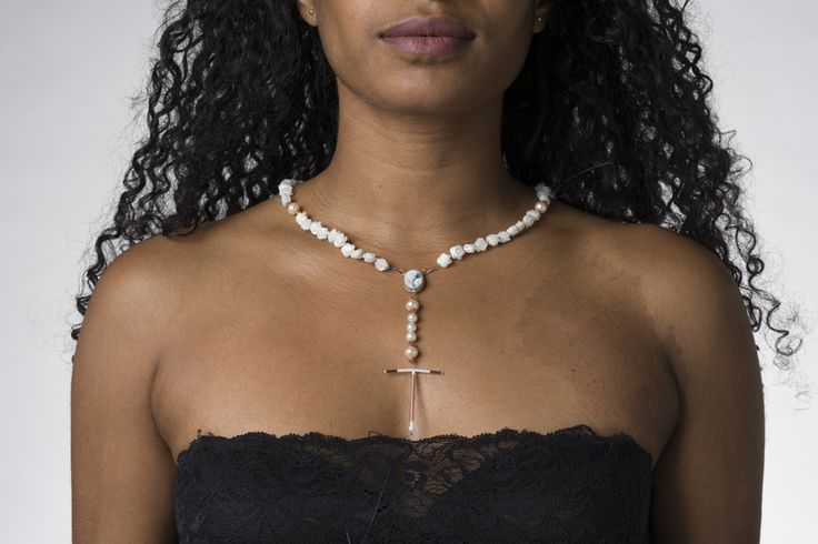 Eva Van Kempen. Necklace: T-Safe, 2017. Copper IUD, cameo (agathe), freshwater pearls, hand cut roses of mother of pearl, faceted sunstone, 14 karat yellow and red gold. Photo by: Hugo Rompa. From series: Ready-to-Bear. On model.