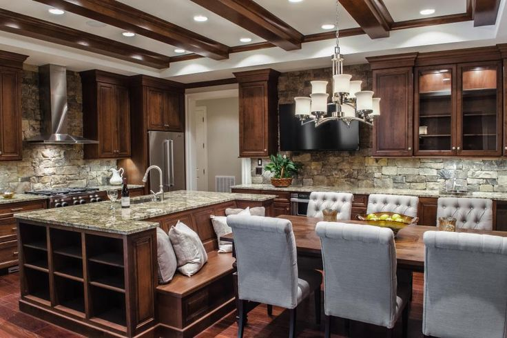 Custom wood cabinets along with a large island with built-in storage make this transitional kitchen as functional as it is elegant. The kitchen island also features a built-in banquette, adding fun and unique seating to the classy, rustic space.