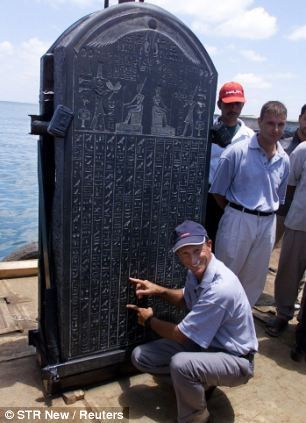 The sunken ancient Egyptian city of Heracleion was submerged by the sea and sands 1200 years ago. Archeologists are now preparing to show some of the objects recovered. --- French marine archaeologist Frank Goddio explains text on the stele of Heracleion on a barge in an Alexandrian naval base