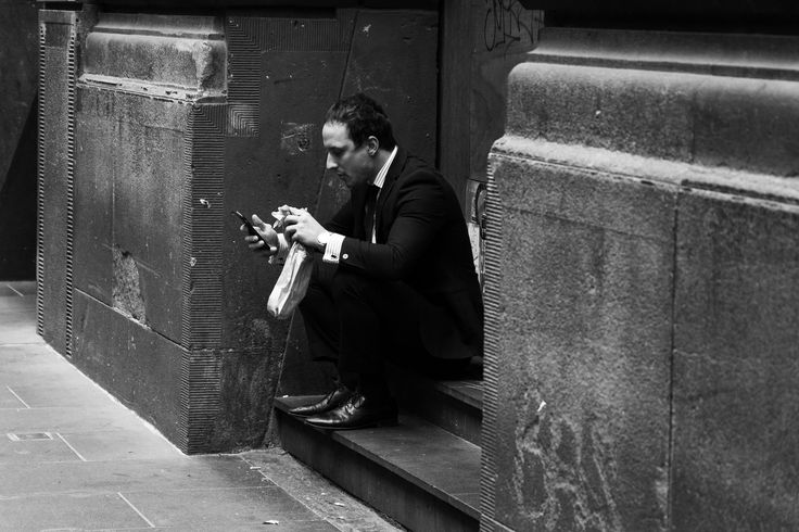 I like this image because even though this man is in his formal business suit he is just simply sitting on a step eating his lunch, occupied by his phone.