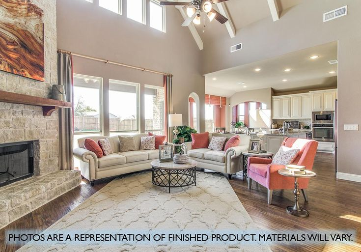 A soaring stone fireplace defines this great room open to the kitchen. The Primrose FE II plan, a new home in the Devonshire community built by Bloomfield Homes. Forney, TX.