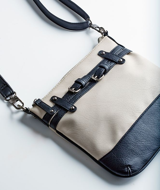 The Black & White Crossbody Bag is a great staple to your wardrobe. With fun buckle designs and a top zip closure, an ideal piece for anyone on the run.