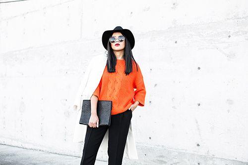 Shop this look on Lookastic:  http://lookastic.com/women/looks/hat-sunglasses-coat-cable-sweater-wide-leg-pants/6902  — Black Wool Hat  — Black Sunglasses  — White Coat  — Orange Cable Sweater  — Black Wide Leg Pants