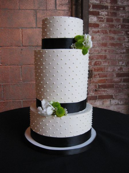 Tall black and white wedding cake with buttercream frosting