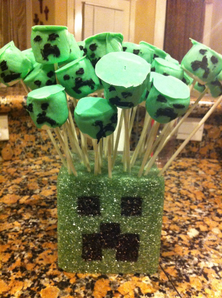 Minecraft creeper Marshmallows dipped in white chocolate bark with green food coloring, then added black frosting face. Green planter styrofoam.