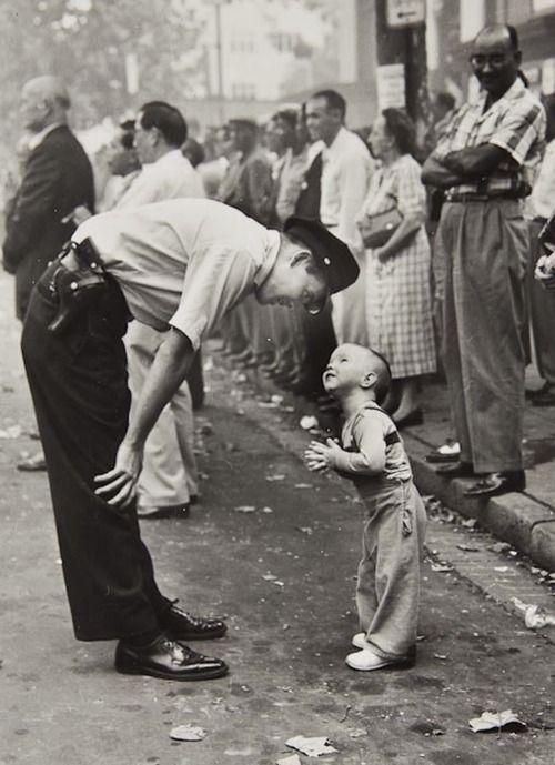 """Durante un festival chino, el oficial de policía Maurice Cullinane intenta convencer al pequeño Allen Weaver para que no cruce la calle durante la explosión de los fuegos artificiales. El fotógrafo era William C. Beall que trabajaba entonces para el Washington Daily News. Llamó a esa foto """"Fe y confianza."""" Fue Premio Pulitzer de 1958."""