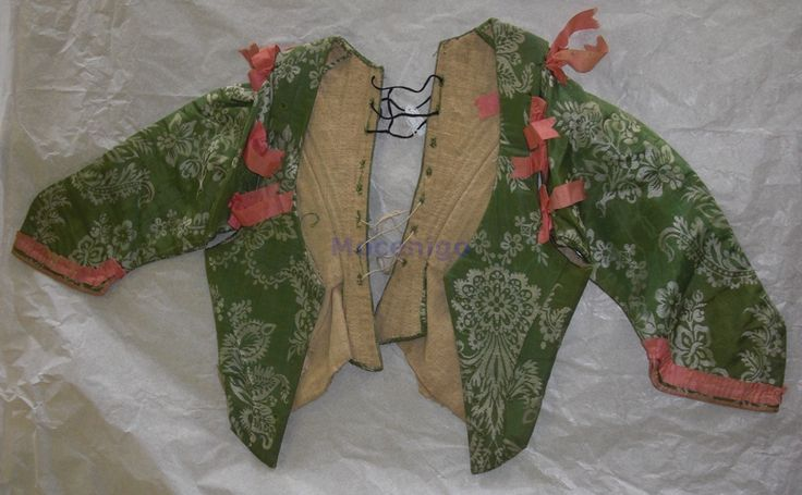 venezia - Corpetto femminile in tessuto operato di seta. Su fondo verde marezzato si distribuiscono in bianco elementi floreali e vegetali fantastici. Sul bordo inferiore delle maniche vi è una guarnizione in nastro rosa. Altri nastri uguali allacciano le maniche alla spalla. Fodera in tela di lino color naturale.
