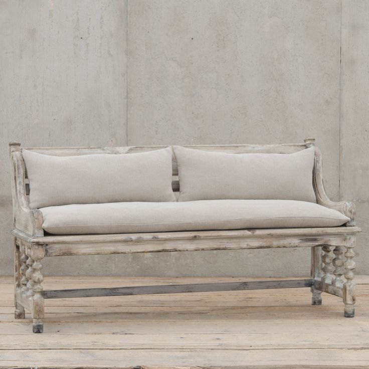 """Effortlessly melding classic European design with farmhouse-chic charm, the Abbey hall bench expresses understated elegance. This detailed furnishing graces living rooms and bedrooms with traditional style and architectural-inspired interest. Linen seat and back cushions provide a plush, neutral touch to the chalk gray frame, accented by a spindle base and artistically curved arms. 63""""W x 23.5""""D x 33""""H. Gray Chalk finish over solid walnut frame. 100% Linen cushions."""