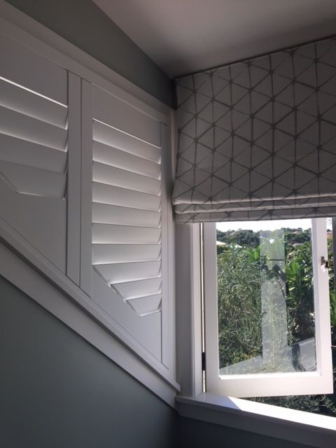 White painted shutters used on an angled window