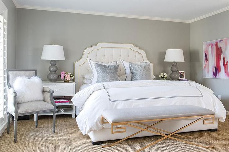 Gorgeous gray and white bedroom with a blue ceiling features a white tufted headboard accented with a gold nailhead trim and supporting a white upholstered bed dressed in gray border hotel bedding topped with gray pillows placed in front of white and gray hotel shams.