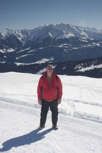 Greg Goldston on the compacted snow hiking trail path from Vorab Gletscher to Nargens enjoying winter walking fun  and sunshine in the snow above Laax, Graubunden, Switzerland