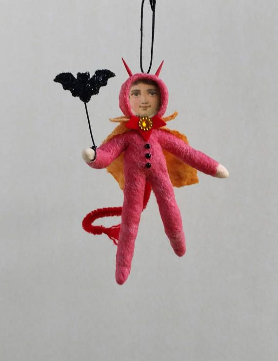 This boy is wearing a red devil costume with amber cape. His horns are toothpicks and his tail a pipe cleaner. He is carrying a black bat. This doll was made from spun cotton and cotton batting over a wire armature. He is 5 tall and hangs on a black cord. The colored cotton was hand dyed. His face is from a vintage German lithograph. Spun Cotton Ornament, Cotton batting doll, Devil boy, Halloween, Plumpuppets