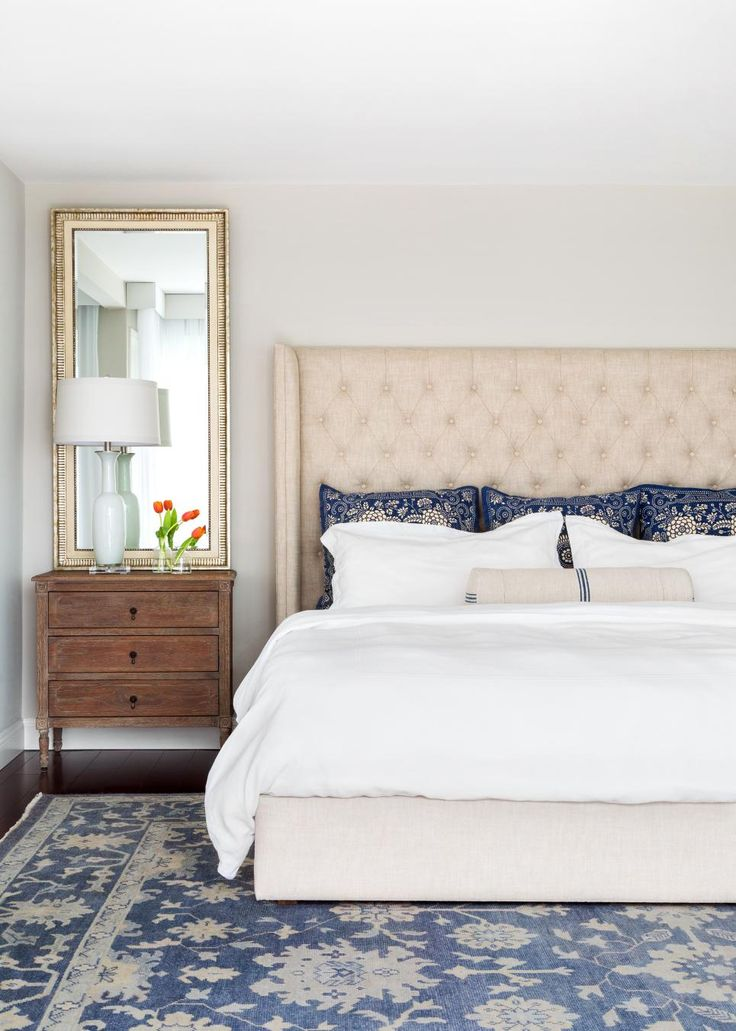 A custom upholstered headboard, tall rectangular mirrors and antique wood nightstands give stately colonial elegance to the master bedroom. Navy blue floral patterns cover the rug and are picked up again in the accent pillows.