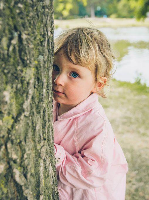 Séance Laetitia, Stéphane et Maëla, photo extérieur Bois de Vincennes, île de Reuilly et Île de Bercy, Maëla qiu se cache derrière un arbre