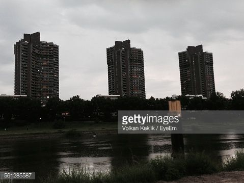 River And Buildings Against Cloudy Sky