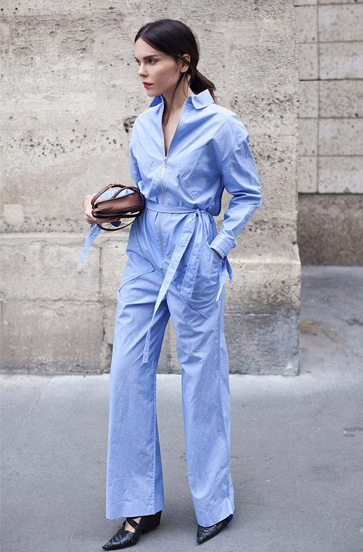 low ponytail, red lips, brown bag and a blue belted utilitarian jumpsuit.