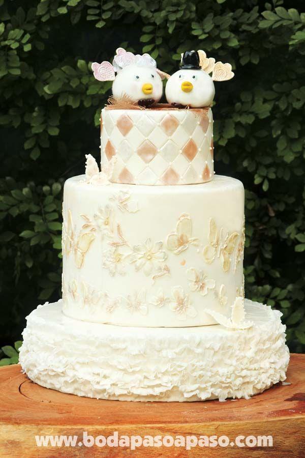 Pastel de tres tortas elaborado en fondant decorado con mariposas y como topper hermosa pareja de avecillas.